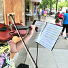 Record-Eagle/Nathan Payne<br /> Emily Long, 16, plays her violin along Front Street while passersby listen. Long, a Traverse City Central High School student, said she bought a permit about 10 days ago and began performing on the street after her music teacher suggested students begin playing outside.
