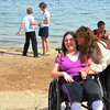 Record-Eagle/Allison Batdorff photos<br /> Left, Brittney Ruckle, 16, left, seated, gets a kiss from her mom, Kris, at Bryant Park on Thursday. The Ruckles are proponents of beach access as it gives them inclusive family  time. Below Elena Kozachik, left, and Samir Moubarak, right, test drive the new beach access at Bryant Park Thursday.