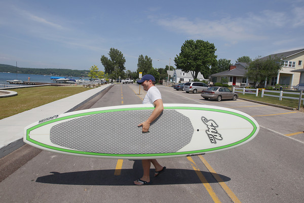 Record-Eagle/Keith King<br /> Greg Olsen, of Traverse City, crosses Lake Street in Beulah Monday, June 24, 2013 as he prepares to go stand-up paddleboarding in Crystal Lake.