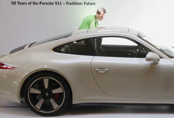 Record-Eagle/Keith King<br /> Rich Rocco, of Illinois, looks at a 2014 Porsche 911 50th Anniversary Edition automobile Friday, June 28, 2013 during the 58th annual Porsche Parade at the Grand Traverse Resort and Spa in Acme. The event, of which Rocco is a participant, concludes Saturday. The last time the Porsche Parade (the annual convention for the Porsche Club of America) took place in Traverse City was 1989. A number of Porsche Parade activities have taken place throughout the week including autocross, rally, an art show and a variety of driving tours.