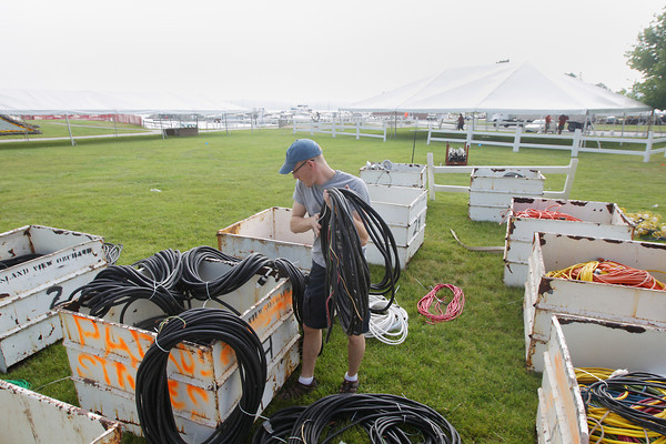 Record-Eagle/Keith King<br /> Craig Fasel, with Robinson Electric, looks for power cords which will be used for air conditioners at the Open Space Tuesday, June 25, 2013 as preparations are made for the National Cherry Festival scheduled to begin Saturday.