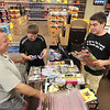 Record-Eagle/Keith King<br /> Clark Gingras, right, totals merchandise for Mike Wood, of Maple City, and his son Dylan Wood, 11, Wednesday at Black Diamond Fireworks in Acme.