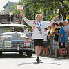 Record-Eagle/Keith King<br /> Tevie Smith, of Vancouver, B.C., Canada, waves American and Canadian flags in front of the 1947 Chrysler he'll drive during the 2012 Great Race.
