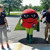 Record-Eagle/Allison Batdorff<br /> The Super Cherry is flanked by Graceland Fruit's Jordan Nye, left, and Brent Bradley, right. The mascot will debut at the National Cherry Festival.