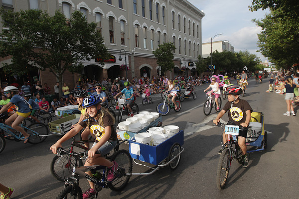 Record-Eagle/Keith King<br /> Bicyclists travel on Front Street Thursday, July 4, 2013 in the Junior Royale Parade during the 87th National Cherry Festival in Traverse City.