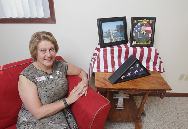 Record-Eagle/Keith King<br /> Christine Stalsonburg sits Tuesday, June 25, 2013 next to photos of her sons, Nicholas Lusby, left, and Barry Lusby.