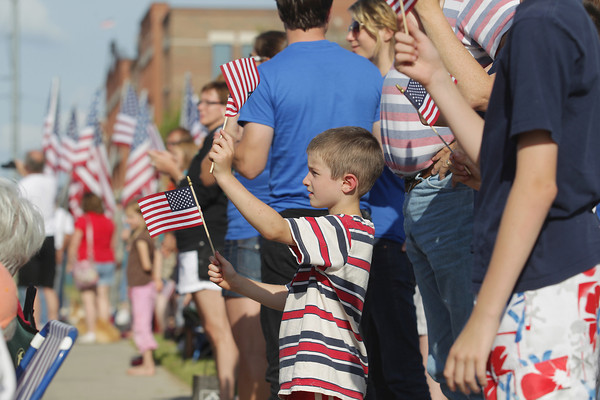 Record-Eagle/Keith King<br /> Nicholas Van Nes, 6, of Traverse City, with others, waves American flags Thursday, July 4, 2013 at the start of the Junior Royale Parade during the 87th National Cherry Festival in Traverse City.