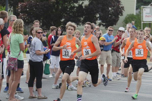 Record-Eagle/Keith King<br /> Jake Keena (33), left, and Anthony Berry (30) race toward the finish line in the high school boys division of the Golden Mile Thursday, July 4, 2013 during the 87th National Cherry Festival in Traverse City.