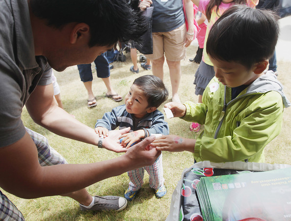 Record-Eagle/Keith King<br /> Abraham Cho, of N.Y. looks at temporary cherry tattoos on the hands of his sons Micah Cho, 2, and Ezra Cho, 5, at the Open Space Saturday, June 29, 2013 during the 87th annual National Cherry Festival.