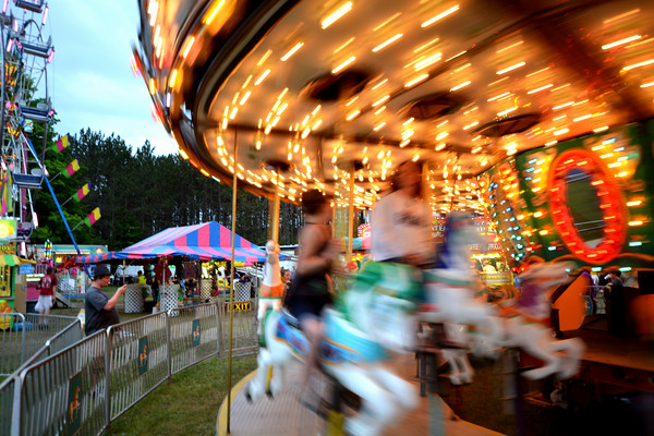 Record-Eagle/Dan Nielsen<br /> Riders spin on the carousel at the Mancelona Bass Festival carnival on Saturday.
