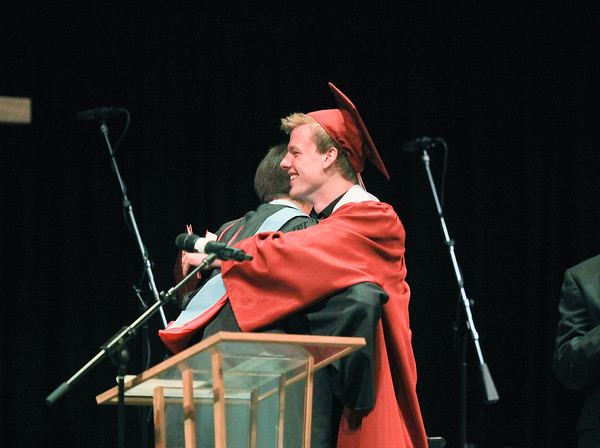 Record-Eagle/Keith King<br /> Benjamin Larkins shares a hug after receiving his diploma and a Bible during the Traverse City Christian High School commencement at East Bay Calvary Church.
