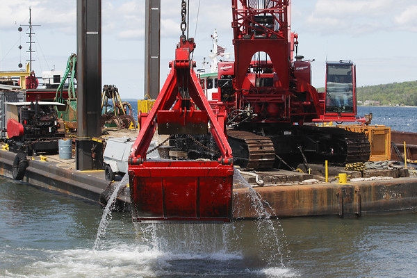 Record-Eagle/Keith King<br /> A crane is used to dredge as improvements, including a new pier, take place in the harbor at the Northwestern Michigan College Great Lakes Campus.