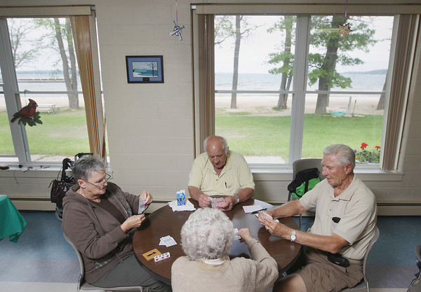 Record-Eagle/Keith King<br /> Barbara Smith, from left, of Traverse City, Les Bowman, of Traverse City, Bill Fickel, of Old Mission Peninsula, and Anne Paulson, bottom, of Traverse City, play pinochle Thursday, June 13, 2013 at the Traverse City Senior Center on West Grand Traverse Bay.