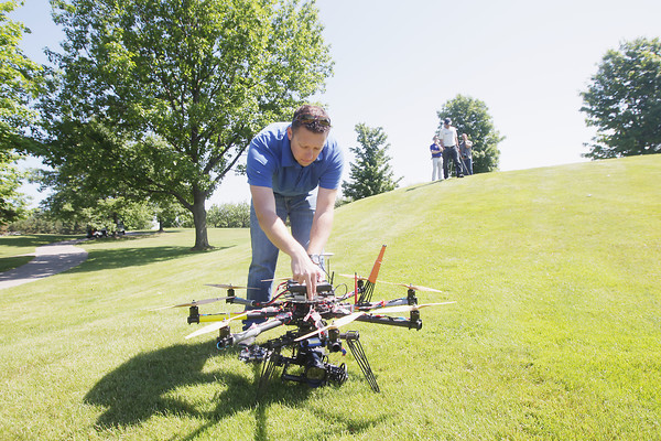 Record-Eagle/Keith King<br /> Tom Knight, lead unmanned aerial vehicle (UAV) pilot and creative director, with EAI, attaches a battery to a CineStar 8 octocopter, an aerial cinematography camera platform, Friday, June 14, 2013 as a promotional video is shot for the Grand Traverse Resort and Spa in Acme with production and direction by Nick Nixon of Nick Nixon Productions.