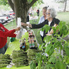 Record-Eagle/Keith King<br /> Callie Cupp, from left, with Guntzviller's Berry and Vegetable Farm, of Elk Rapids, assists Linda Borish, of Pa., and Hanna Patterson, of Traverse City, Monday, June 10, 2013 during the Village at Grand Traverse Commons Farmers Market. The market is scheduled for Mondays from 3:00 p.m. until 7:00 p.m. until the end of October when the market will take place indoors at the Village at Grand Traverse Commons.