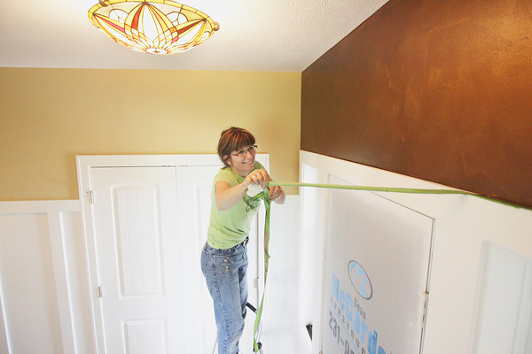 Record-Eagle/Keith King<br /> Lynette Flowers, owner of Painted Expressions, removes tape from above a door Thursday, June 6, 2013 as she works in a new house in the Verndale at East Bay neighborhood in East Bay Township. The house will be in the 2013 Parade of Homes.