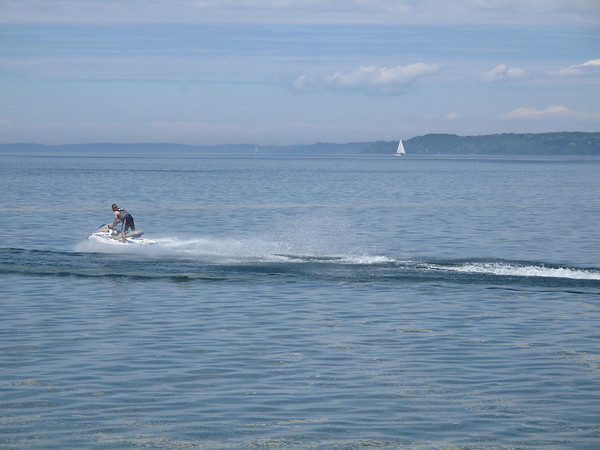 Glenn Puit/Record-Eagle<br /> A man races his personal watercraft across Grand Traverse Bay Wednesday as a sailboat floats in the background.