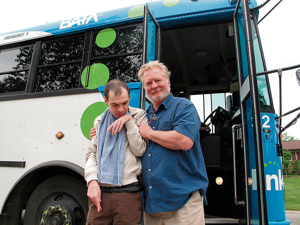 Record-Eagle/Anne Stanton<br /> Bus aide Kevin Wynkoop helps Michael Hauler off the bus. Michael's mother, Jeanine Rossbach, praised Wynkoop as observant and helping her son when he suffers seizures.