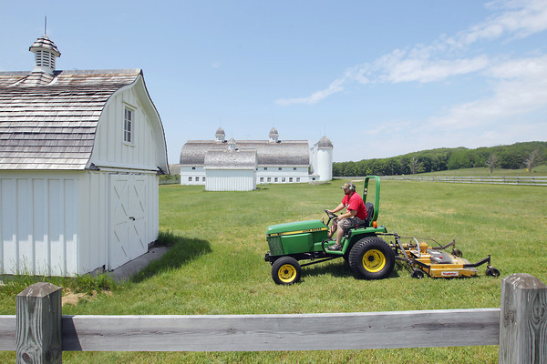 Record-Eagle/Keith King<br /> BJ Tvardek, with the Crystal River Corporation, operates a tractor with a mowing implement as he mows Monday, June 10, 2013 at the historic D.H. Day farm in Glen Arbor Township within the boundaries of the Sleeping Bear Dunes National Lakeshore.
