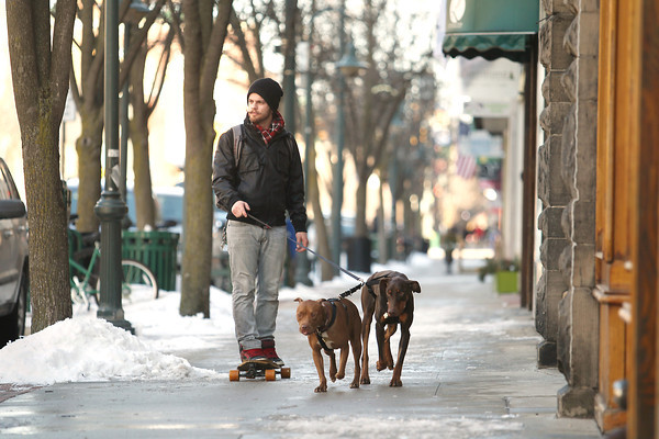 "Record-Eagle/Keith King<br /> Nathan Hayes, of Traverse City, and his dogs, Lucy, left, and Woody, right, travel Thursday, March 14, 2013 through downtown Traverse City. Hayes also utilized the TART Trail on his outing. ""This is the first day the TART Trail has been clear enough to ride my longboard,"" Hayes said. Lucy and Woody are rescue dogs."