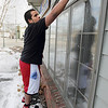 "Record-Eagle/Keith King<br /> Isaiah Camacho, 16, of Suttons Bay, working for Moses' Window Cleaning, washes windows at Olde Towne Plaza in Traverse City. ""I'm the type of guy that's always wearing shorts,"" Camacho said. ""Today I was glad I could come out and work and make some money."""