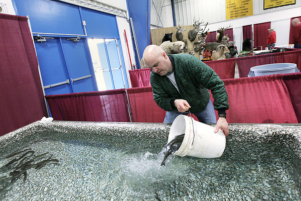 Record-Eagle/Keith King<br /> Brian Kuhr, of Traverse City, dumps hybrid rainbow trout into a pool of water for the Traverse City Hunting & Fishing Expo.