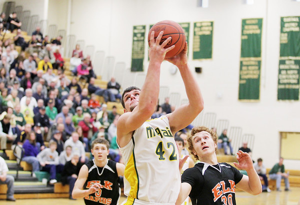 Record-Eagle/Keith King<br /> McBain's Cody King maintains control of the ball prior to shooting against Elk Rapids' Broc Crandall (30) and Luke Morrison (3).