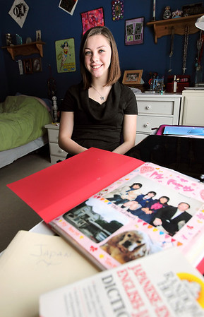 Record-Eagle/Keith King<br /> Hollie Dowd, 15, of Solon Township, sits in her room Wednesday near a scrapbook she received from a family in Japan that would be one of her host families if she chooses to become an exchange student there.