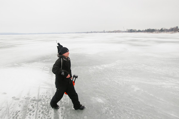Record-Eagle/Keith King<br /> Eli Waterman, of Kingsley, carries his gear off the ice after ice fishing Thursday on West Grand Traverse Bay.