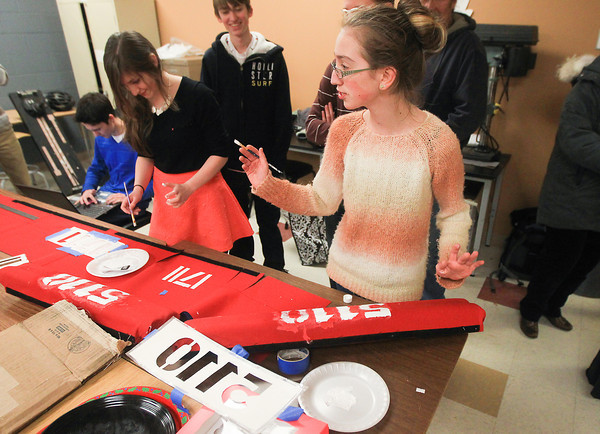 Record-Eagle/Keith King<br /> Keely Golden, left, 16, of the Traverse City Central High School robotics team, along with Caitlin Scroggins, right,16, of the Elk Rapids High School robotics team, work on painting team numbers onto bumper covers as Jackson McKay, from back left, 17, and R.J. Fenton, 16, both of the Traverse City Central High School robotics team, also prepare for the Escanaba FIRST (For Inspiration and Recognition of Science and Technology) Robotics District Competition.