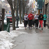 Glenn Puit/Record-Eagle<br /> Students from Traverse City Central High School run down Front Street in downtown Traverse City Monday afternoon as snow starts to fall.