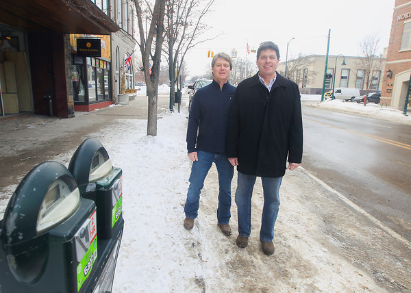 Record-Eagle/Keith King<br /> Matt Davies, left, and Mark Davies, owners of Union Cantina, back left, stand Friday at a parking space on Union Street in downtown Traverse City.