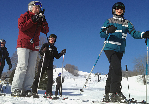 """Record-Eagle/Nathan Payne<br /> Karen Keranen, left, straps on her helmet before hitting the slopes at Crystal Mountain Resort and Spa with a group of """"Retired not Tired"""" ski club members. An accomplished instructor, Keranen is one of a handful of leaders who help reintroduce seniors to downhill skiing."""