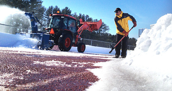 """Record-Eagle/Nathan Payne<br /> Traverse City Central High School track coach John Lober shovels slush from the orange track surface at the school while Jeff Dean, owner of Old Mission Snow Blowing, shoots 3-foot-deep snow away from the lanes. Lober decided to enlist help from Dean after he realized the snow was so deep on the track that it likely wouldn't melt until weeks into the upcoming spring season. Practices are scheduled to begin Monday, said the veteran coach.<br /> """"This is the most snow we've ever had,"""" Lober said. """"This is my gauge of winter."""""""