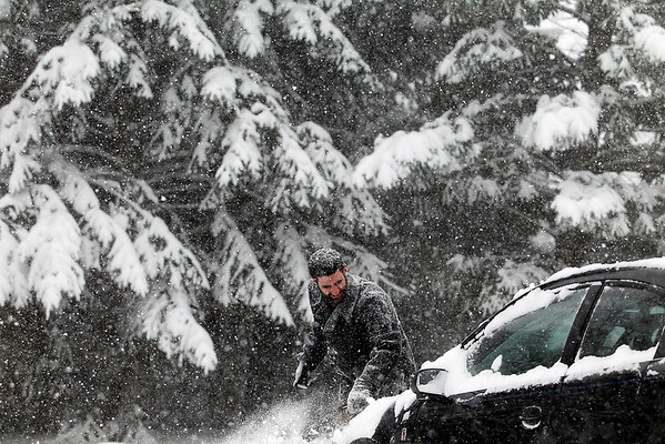 Record-Eagle/Jan-Michael Stump<br /> Andrew Franzo brushes snow off his car before going to work on Wednesday afternoon during a period of heavier snowfall.