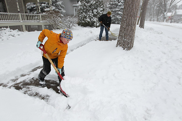 Record-Eagle/Keith King<br /> Max Werner, 8, of Traverse City, and his father, Tim, shovel snow along the sidewalk in front of their home on Wednesday.