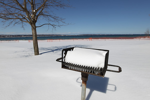 Record-Eagle/Keith King<br /> Snow lies on a grill Thursday, March 24, 2011 at Bryant Park in Traverse City.