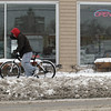 Record-Eagle/Keith King<br /> John Bedwell, of Traverse City, walks his bike through snow Wednesday, March 23, 2011 along Eighth Street. Bedwell was on his way to help a friend shovel snow from his driveway.