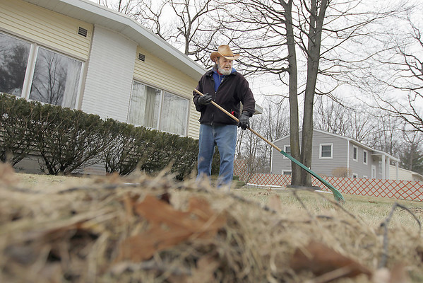 """Record-Eagle/Keith King<br /> Ron Sheffer, of Traverse City, rakes leaves and debris for his neighbor and himself Tuesday in front of the duplex he lives in. """"It's good working weather,"""" said Sheffer, who used to be an employee for the City of Traverse City before retiring after 32  years."""