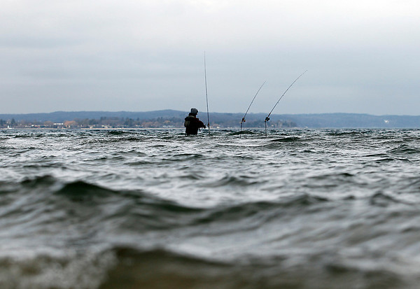 Record-Eagle/Jan-Michael Stump<br /> An angler fishes at the mouth of the Boardman River in West Grand Traverse Bay on Monday afternoon.