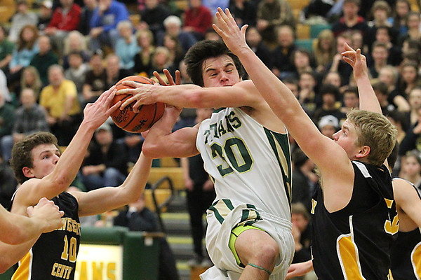 Record-Eagle/Jan-Michael Stump<br /> Traverse City West's Zach McGuire (30) tries to drive between Traverse City Central's Taylor Cook (10) and Mitch Wynkoop (52) in the second quarter of Monday's district game.