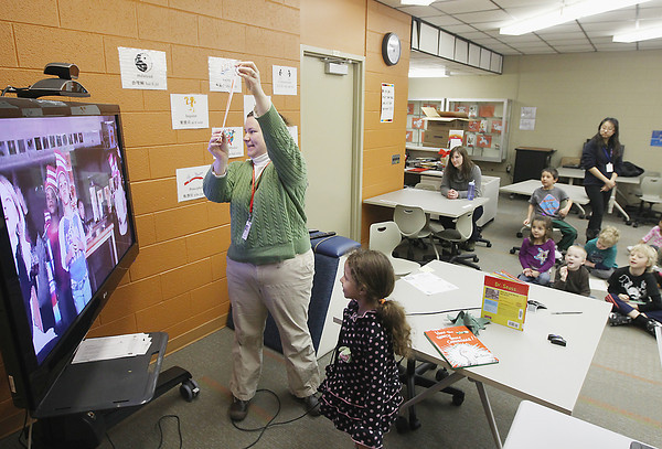 Record-Eagle/Keith King<br /> Alicia Rowney, kindergarten/first-grade teacher at International School at Bertha Vos, holds up a picture made by Angelina VanKommer, bottom, Tuesday, March 5, 2013 to show students in Pittsburgh, Pa. using telecommunications and video. The two classes were talking about subject matter relating to Dr. Seuss.