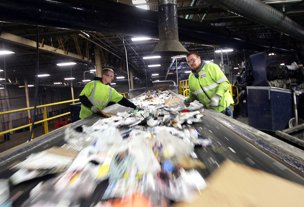 Record-Eagle/Keith King<br /> Joshua Reinhart, left, and Travis Grooten, sort recycling commodities Thursday, March 7, 2013 at the American Waste facility on Hughes Drive in Traverse City.
