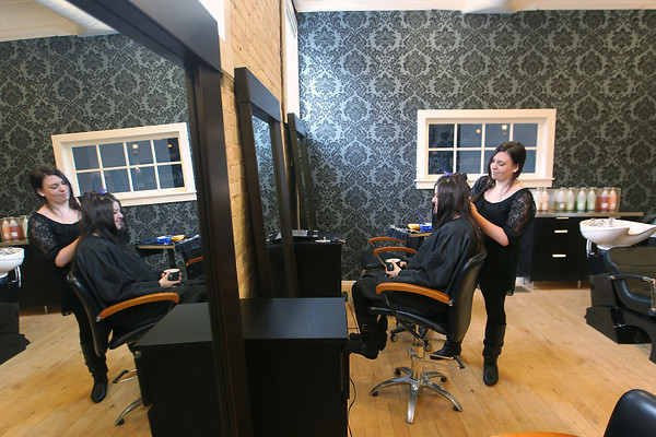 Record-Eagle/Jan-Michael Stump<br /> Stylist Whitney Larson (cq) colors and styles the hair of Alicia Troup (cq) Thursday at The Exchange, a boutique and salon on Union Street in downtown Traverse City.
