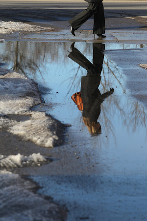 Record-Eagle/Jan-Michael Stump<br /> Lindsey Dickinson of Traverse City walks past a puddle and melting snow along West Front Street on a sunny Monday afternoon. This week is forecast to see temperatures in the mid-to-upper 30s.
