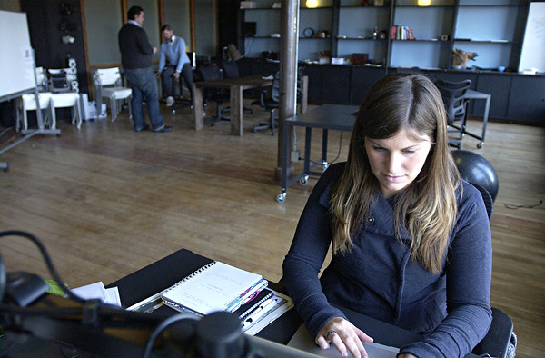 Record-Eagle/Nathan Payne<br /> Kirsten Matson works at a desk at CoWarf, a coworking space she opend with her husband Bradley last year. The Matsons opened the second-floor space to allow workers to rent a desk for a day, week or month without all the other costs of leasing an office.