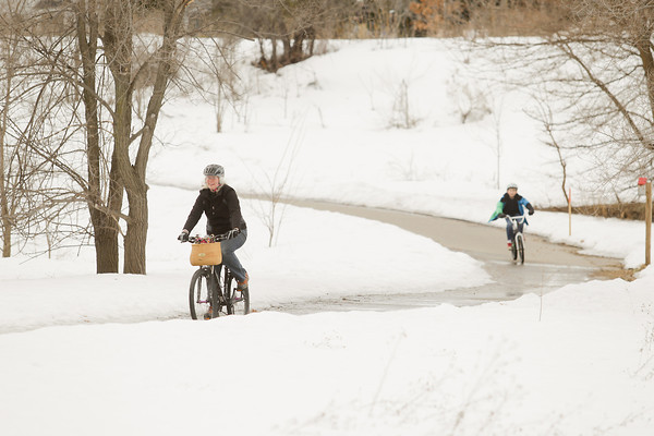 Record-Eagle/Keith King<br /> Jill Kiteley and Harrison Kiteley, 9, of Traverse City, ride bicycles in mild temperatures Monday as they travel along the Boardman Lake Trail in Traverse City.