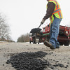 Record-Eagle/Keith King<br /> Jeff Hall, with the Grand Traverse County Road Commission, repairs a pothole on M-186 in Fife Lake Township.
