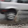 Record-Eagle/Keith King<br /> A vehicle hits a pothole along Munson Avenue south of Eighth Street in Traverse City.