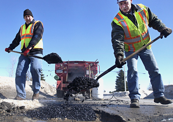 """Record-Eagle/Nathan Payne<br /> Larry Oster and Joe Longton scoop shovels full of """"cold patch"""" from a heated trailer into deep potholes on Heritage Way near Zimmerman Road. The men who work as seasonal workers for the Grand Traverse County Road Commission spent the day Tuesday packing about four tons of patch material into dozens of potholes on area roads. """"It's only going to get worse,"""" Oster said, heaving another scoop full of the mixture into a nearby tire-eating hole."""
